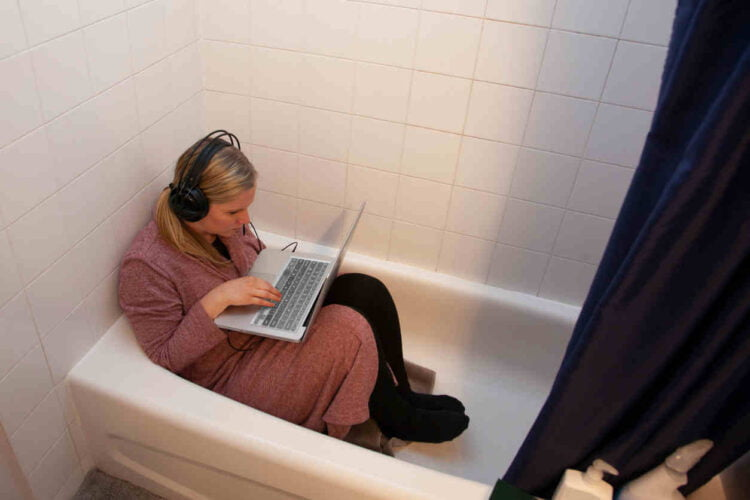 person gets creative working from home in the bathrub