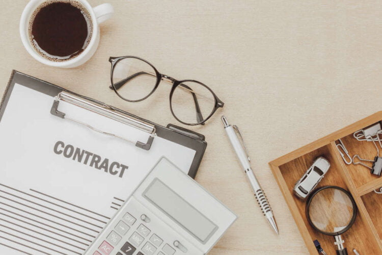 top view business contract form with coffee eyeglasses car calculator pen with magnifying glass on wooden background